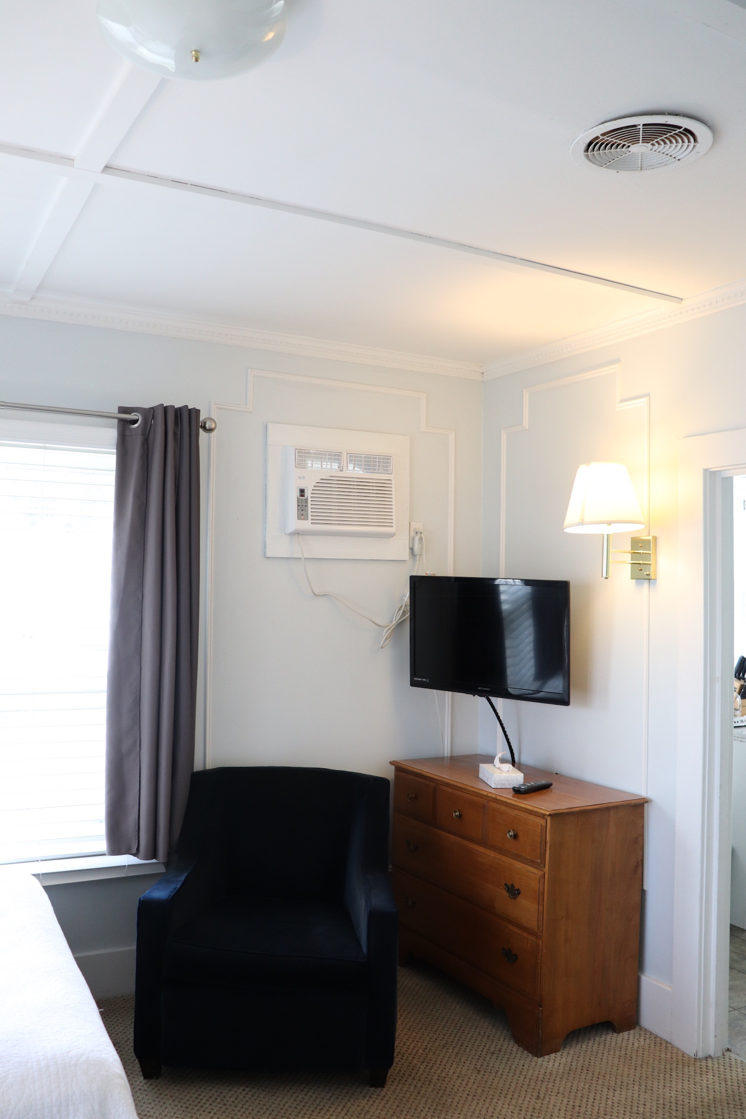 Wall-mounted TV above dresser with chair